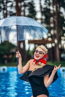 Pin up styled blonde in sunglasses holding umbrella and have fun in the swimming pool