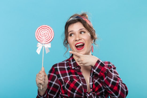 Pin-up woman, fashion and people concept - portrait of pin-up woman with lollipop over the blue background.