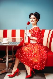 メイクアップを持つ女性をピンで留める赤いバラ