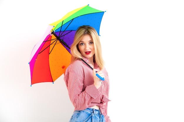 白い壁の背景にカラフルな傘を保持している赤い口紅と市松模様のシャツのピンナップ若いかわいい女性、スタジオショット