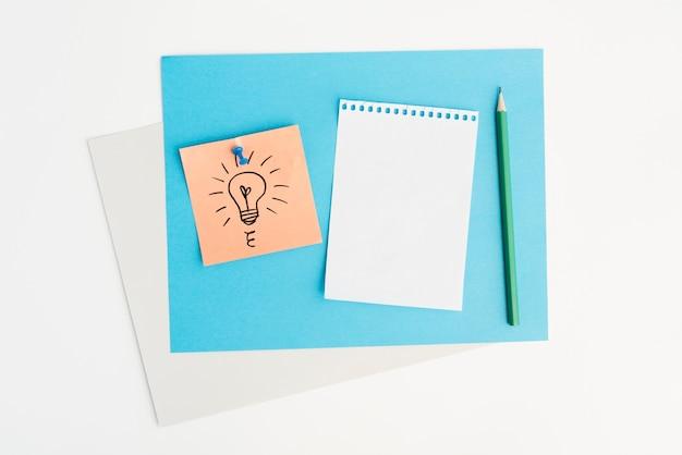 白い背景の上に画pinで接続されている付箋に描かれた電球の高角度のビュー