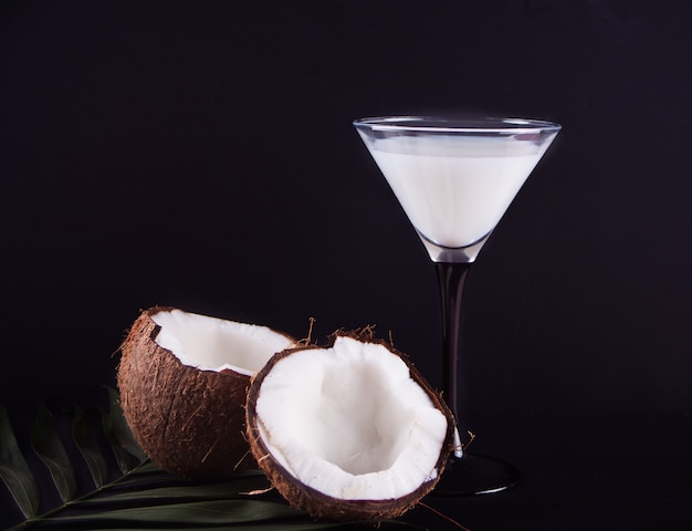 Pina colada cocktail with palm leaf and coconut on the black background