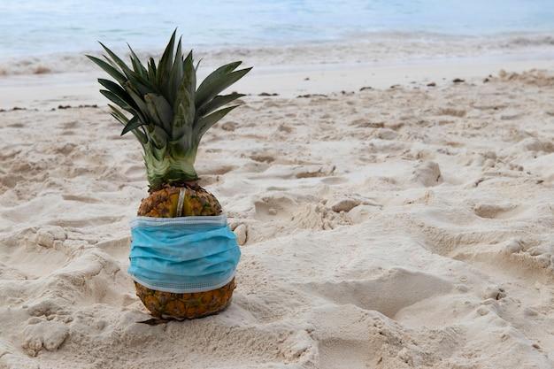 カリブ海沿岸の砂浜にある保護フェイスマスクのパイナップルでピニャコラーダを飲みます。検疫中の休暇と旅行の概念。
