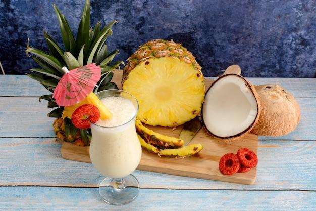 Пина колада со свежими фруктами на деревянной разделочной доске на белом столе и синем фоне
