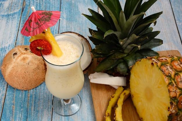 Пина колада со свежими фруктами на деревянной разделочной доске на фоне стола белой доски