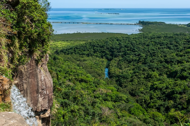 Pinaisara waterfall river flowing between mangrove forest gradient blue sea iriomote island