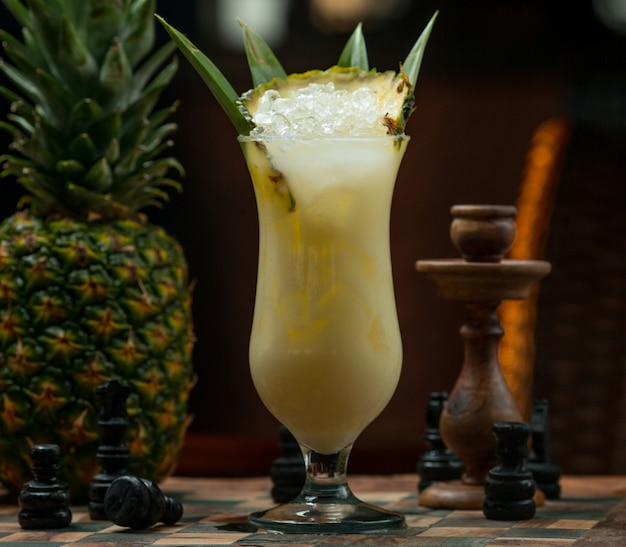 Pinapple ice cold cocktail glass on a chess board