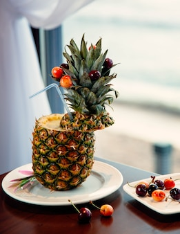 Pinapple juice cocktail with fruits and berries inside cone.