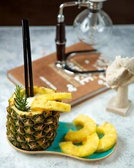 Ананасовый сок взбить с соломой и ломтиками ананаса