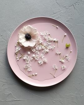灰色のテーブルにアネモネの花とネギの花とピンチプレート。上面図、フラットレイスタイル。
