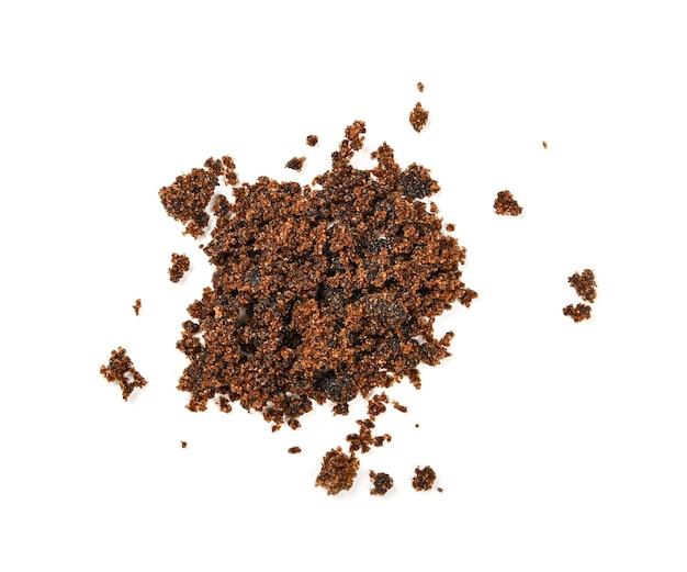 Щепотка коричневого мусковадоканового сахара разлилась, изолирована на белом фоне, крупным планом, вид сверху
