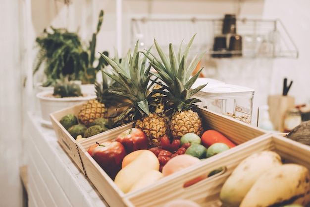 Pine apple, mango, apple and various types of fruit in wooden box.