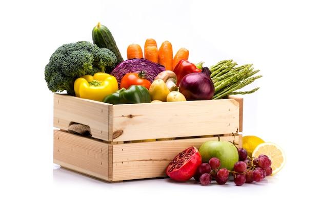バランスの取れた食事に最適な白い背景にカラフルな新鮮な野菜でいっぱいの松の箱