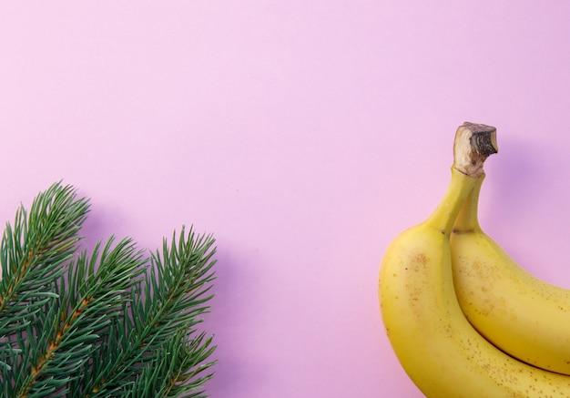 ピンクの背景に松の枝とバナナの半分。クリスマス休暇のコンセプト