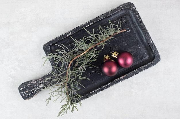 暗いボード上の松の枝と光沢のあるボール