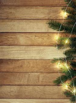 Сосновая ветка с огнями на деревянном столе