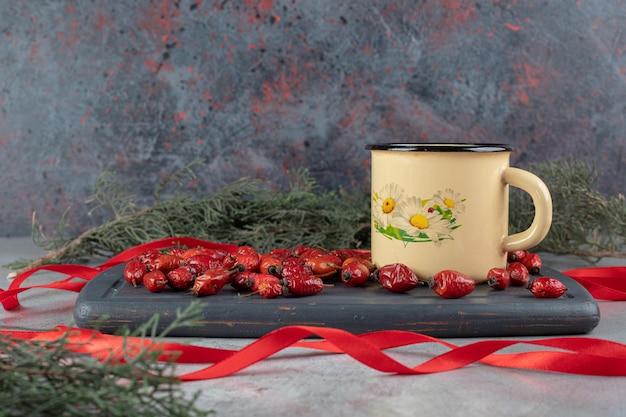 Сосновые ветки рядом с темно-синим подносом с плодами шиповника и кружкой чая из шиповника, окруженные лентами на мраморной поверхности