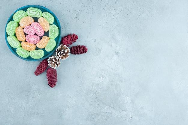 Disposizione a pigna e piatto di marmellate su marmo.
