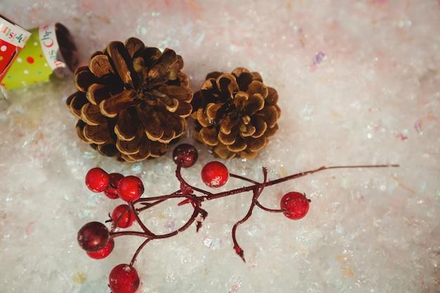 Шишка, вишня и рождественские крекеры на снегу