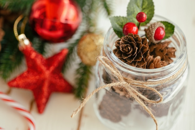 Pine cone or conifer cone and red holly balls in glass bottle with rustic ribbon bow tie. christmas background with festive decoration red sparkle star shape and bauble ball for christmas wallpaper.
