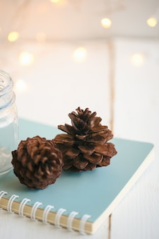 Pine cone or conifer cones on blue notebook near bottle glass on rustic white wood plank with golden light bokeh backdrop. sweet vertical background for christmas and winter season wallpaper.