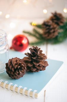 Pine cone or conifer cones on blue notebook near bottle and red bubble ball on white wood plank with golden light bokeh backdrop. sweet vertical background for christmas and winter season wallpaper.