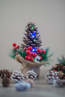 Pine cone decorated with holly berries and lights on wooden table.