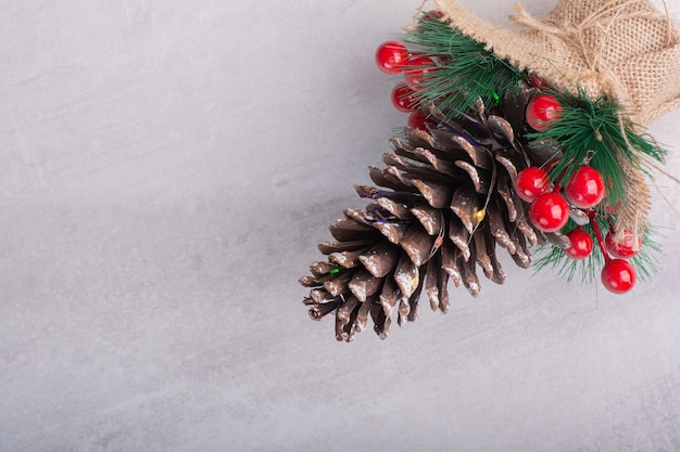 Pine cone decorated with holly berries and snowflake on white surface