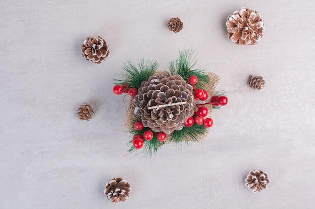 Cono di pino decorato con bacche di agrifoglio e fiocco di neve sul tavolo bianco