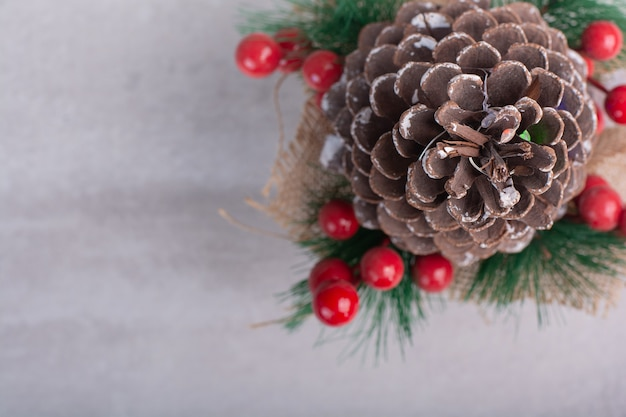 Pine cone decorated with holly berries and snowflake on white table