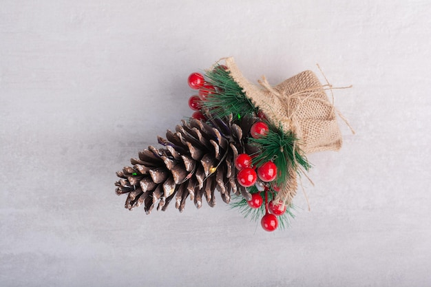 Pigna decorata con bacche di agrifoglio e fiocco di neve sul tavolo bianco.
