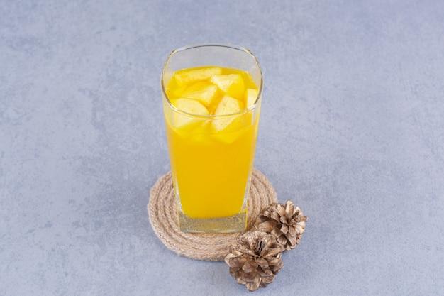 大理石の上に松ぼっくり、ジュースとトリベットのグラス。