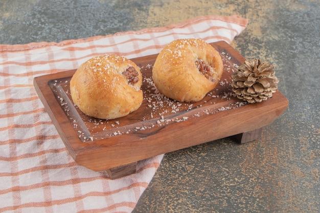 Сосновая шишка рядом с двумя вкусными печеньями на деревянной доске на мраморе.