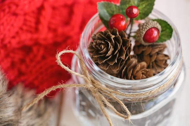 Шишка или шишка и красные шары в стеклянной бутылке с деревенской лентой галстук-бабочку. рождественские фон с праздничные украшения красные трикотажные шерстяные перчатки для рождественских обоев.