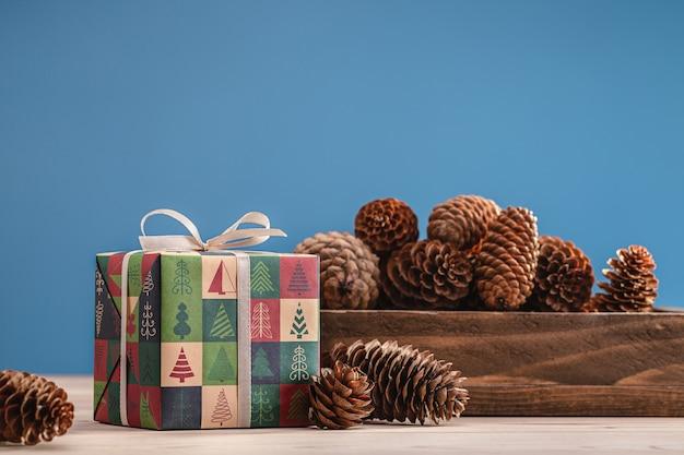 冬の飾りが付いた箱に詰められた松ぼっくりのクリスマスと新年の贈り物。愛する人へのサプライズやお土産のコンセプト