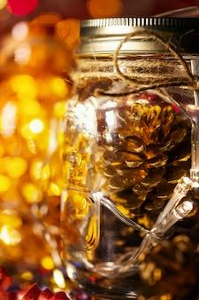 ガラスの瓶、クリスマス装飾背景の松ぼっくり。