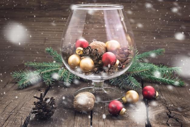 木製の背景のガラスの松ぼっくり、ナッツ、クリスマスのおもちゃ。着色。降雪