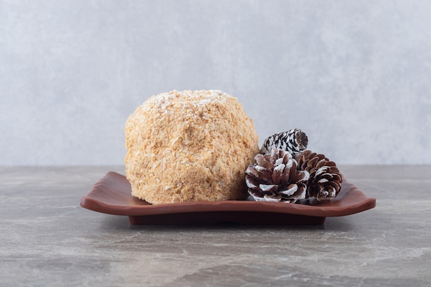 Pine cones and a squirrel cake on a brown platter on marble surface