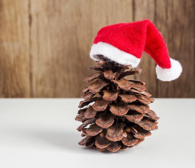 Сосновые шишки с рождественскими шляпами на дереве