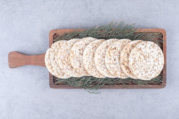 大理石のテーブルの上のクッキーのトレイを飾る松の葉。