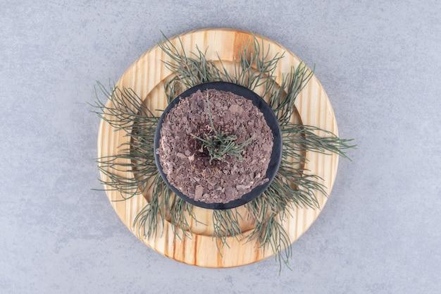 소나무 잎과 대리석 테이블에 나무 접시에 케이크.