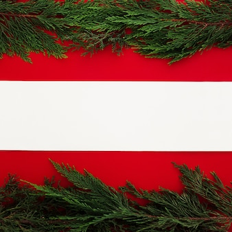 Pine leaves on a red background with a blank note
