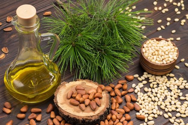 Ядра кедровых орехов в деревянной коробке и на столе. кедровые орехи в скорлупе. бутылка масла.
