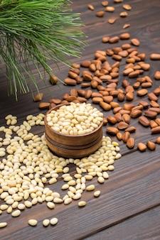 Ядра кедровых орехов в деревянной коробке и на столе. кедровые орехи в скорлупе. кедровая ветка. темный деревянный фон. вид сверху