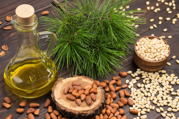 Pine nut kernels in wooden box and on table. inshell pine nuts. bottle of oil.