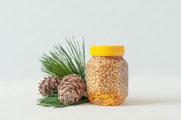 Кедровый орех с медом в прозрачной банке с желтой крышкой. рядом сосновые шишки и хвоя. место для метки. крупный план. светлый фон.