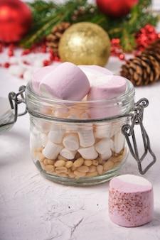 Кедровые орехи и зефир в банке на белой поверхности, шишка, еловые ветки, елочные шары и украшения на фоне