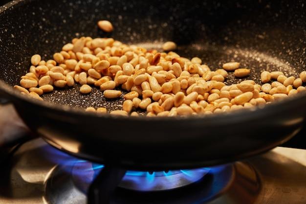 Кедровые орехи обжариваются на сковороде, чтобы получился пирог с мангольдом. пошаговый рецепт.