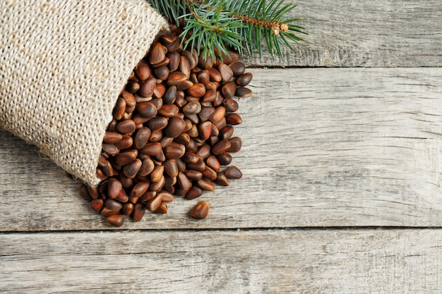 Pine nuts in a bag of burlap with a fir green branch. in country style.