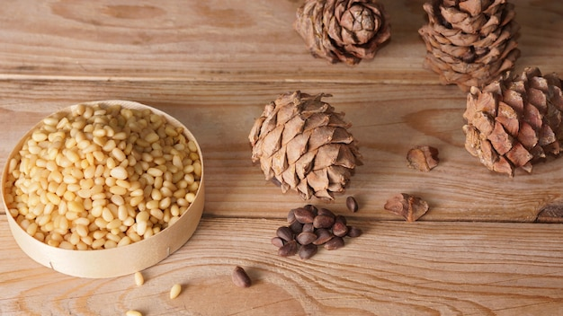 Pine nuts and cedar cones are on a wooden table.
